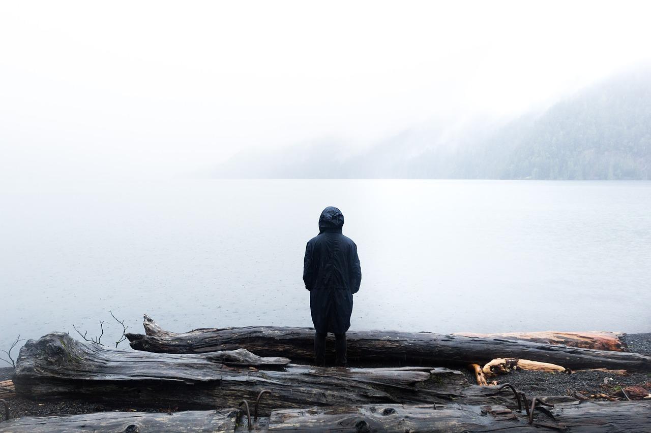 Mensch im Nebel an einem See schaut in die Weite und spürt Kraft in sich - die Resilienz