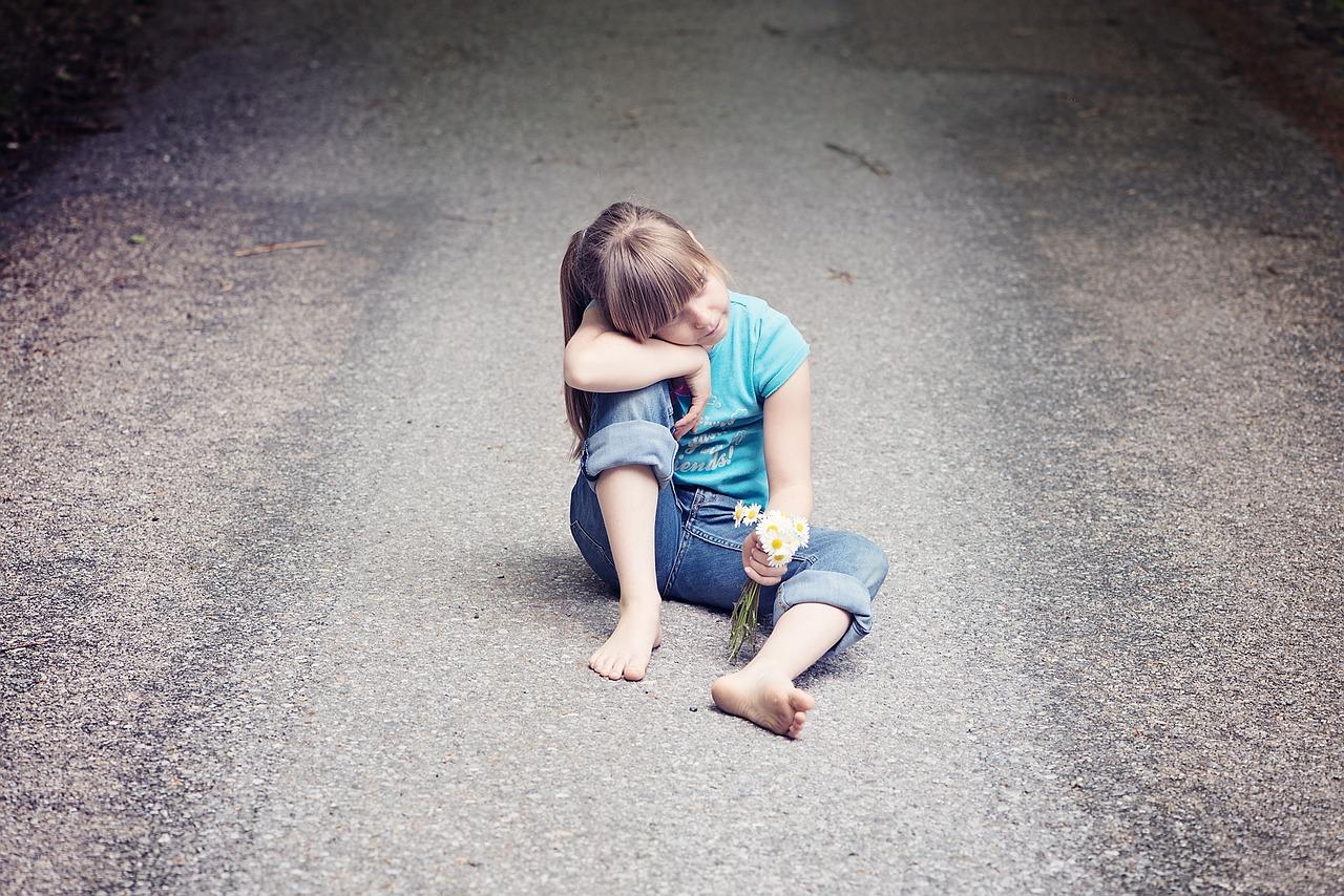 Kleines Mädchen sitzt auf einer Straße mit Blumen in der Hand als Sinnbild für unser inneres Kind