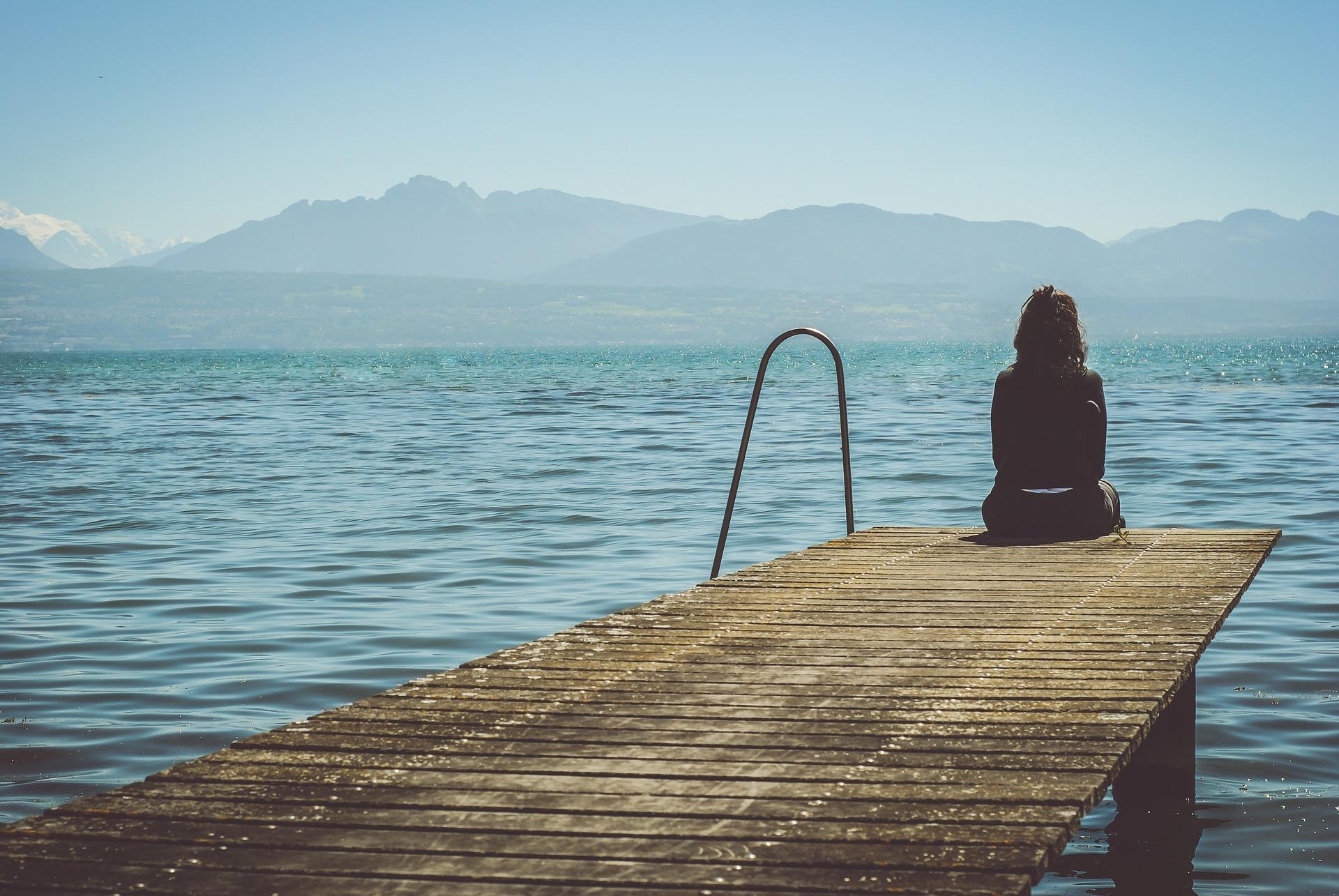 Frau sitzt auf einem Steg am Wasser, schaut ruhig in die Berge als Sinnbild dafür, wie man seine Depression überwinden kann