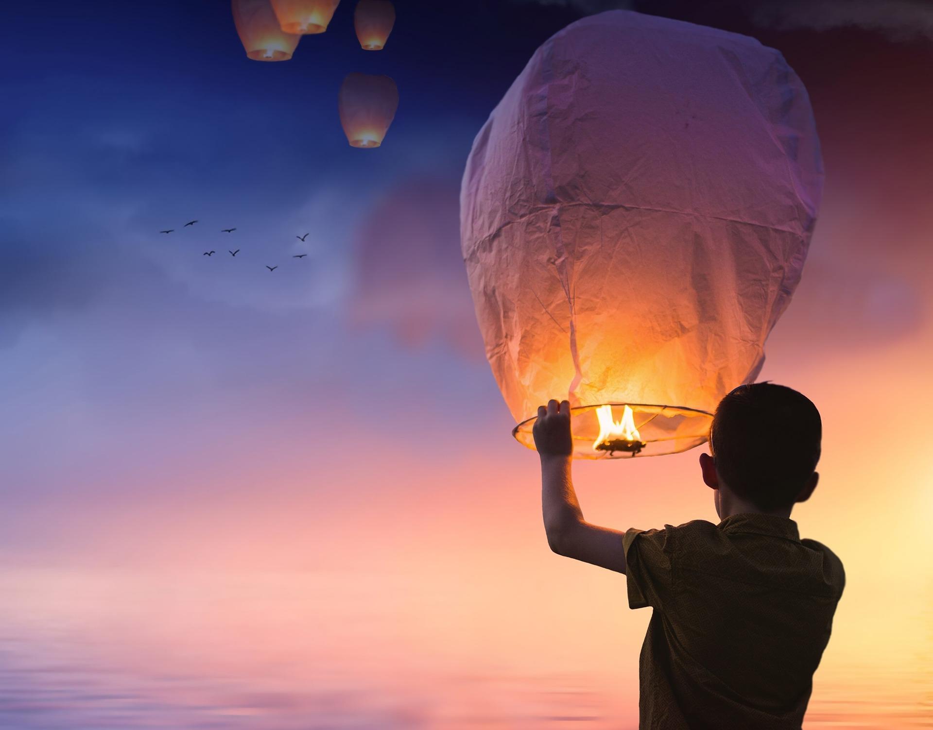 Junge der ein Licht in den Himmel aufsteigen lässt als Sinnbild für das Loslassen