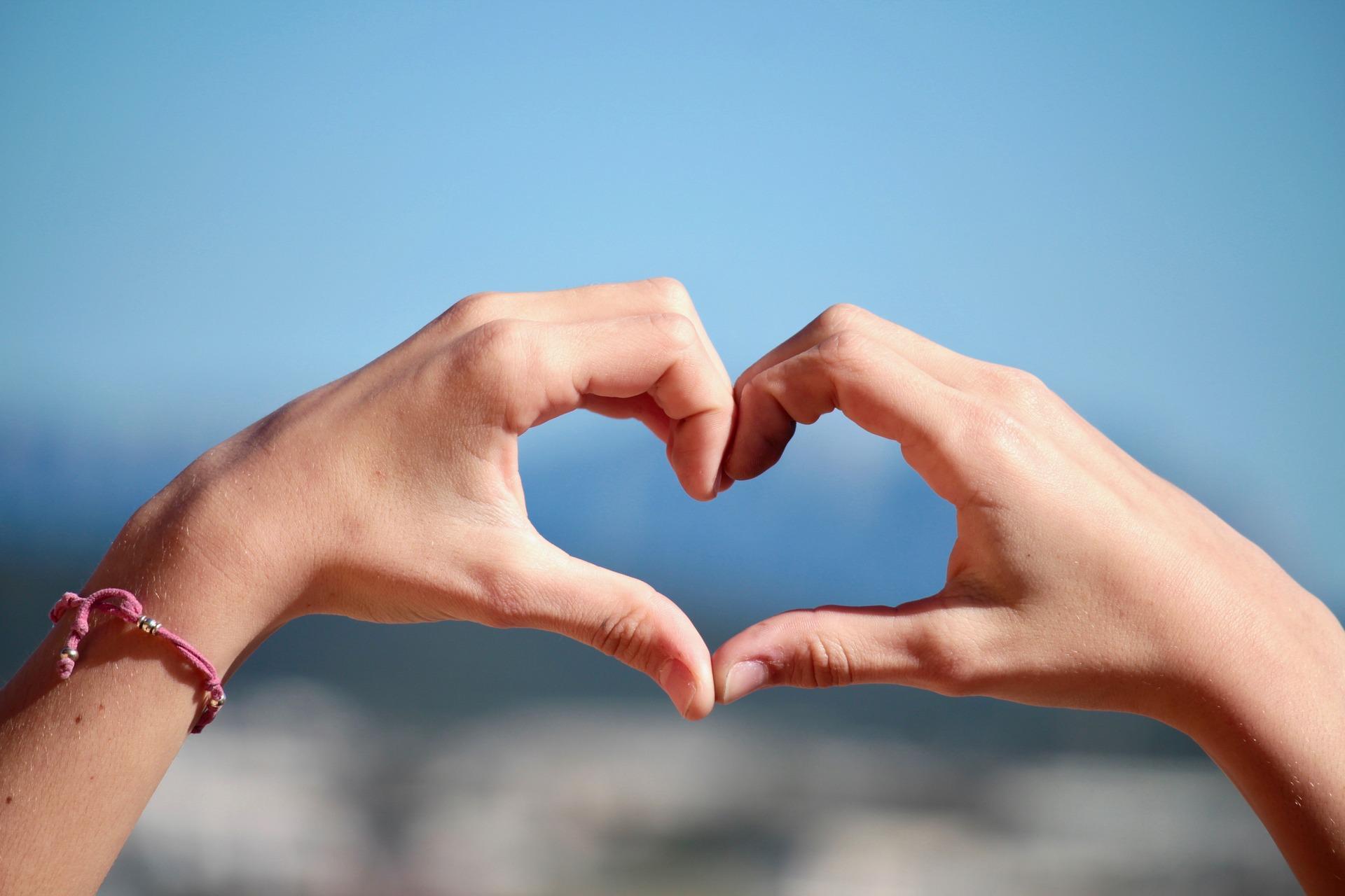 Zwei Hände formen ein Herz vor blauem Himmel als Sinnbild für Herzintelligenz