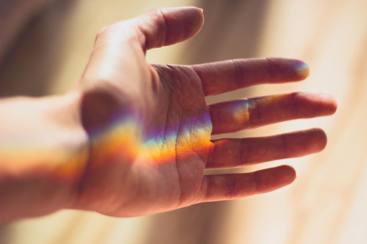 Seitlich geöffnete Hand mit Regenbogenstrahlen, die darauf scheinen