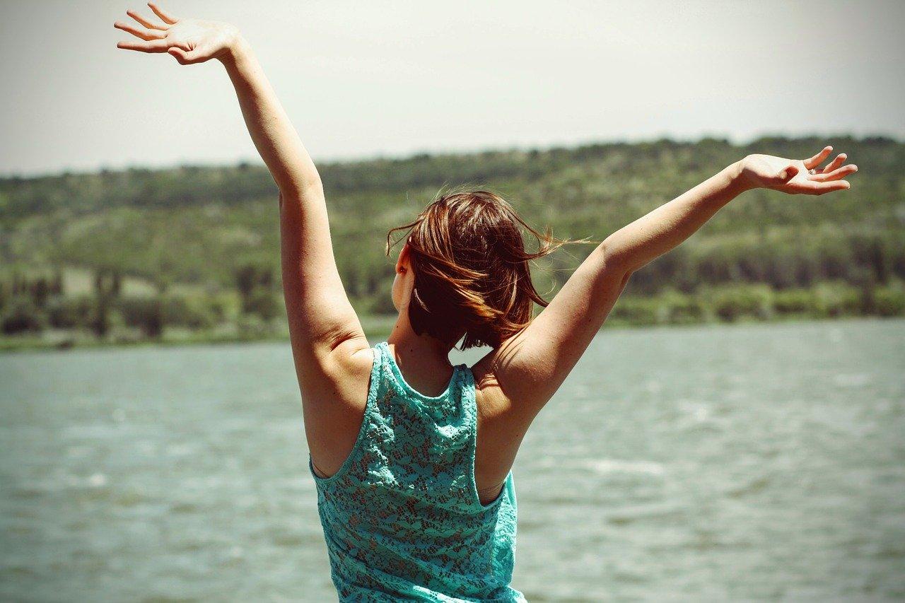 Frau im grünen Top von hinten zu sehen am Wasser wirft die Arme in die Luft