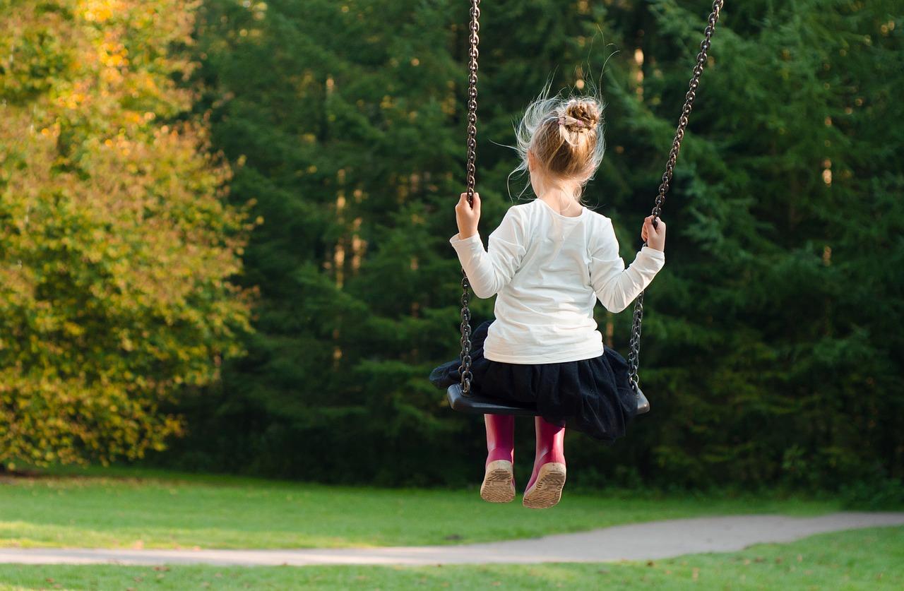Kleines Mädchen mit roten Gummistiefeln auf einer Schaukel als Sinnbild für das innere Kind und seine magische Kraft