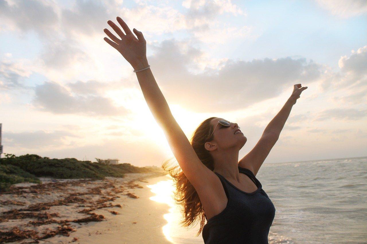Frau am Strand hebt die Arme in den Himmel um das Leben zu feiern und weiß, so kommt das Glück zu ihr