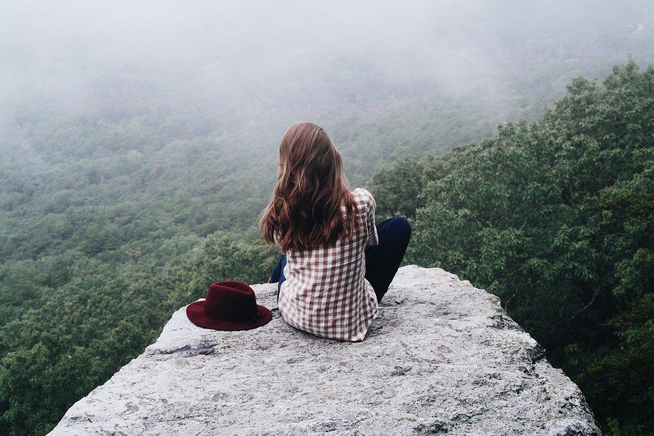 Frau von hinten zu sehen auf einem Felsblock, den Hut neben sich, sie schaut über Bäume und weiß, dass mit Mut die schönsten Geschichten anfangen