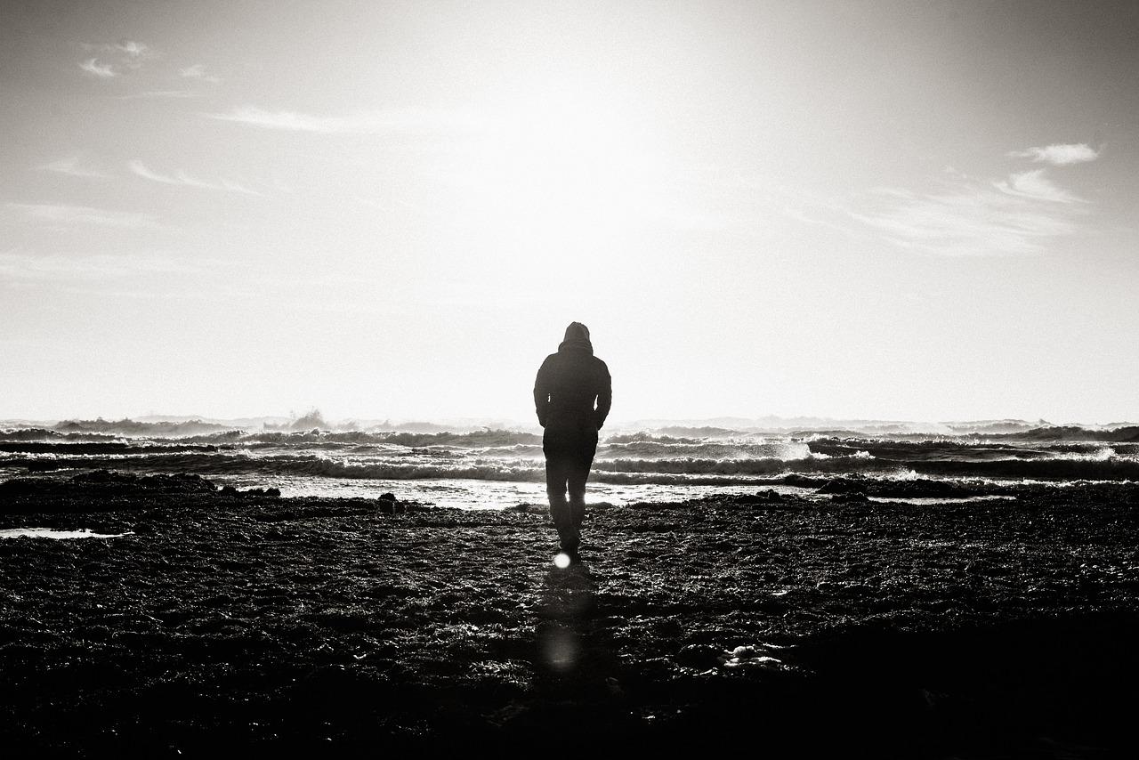Mann am Strand in schwarz-weiß, die Wellen vor ihm als Sinnbild für Gedanken, mit denen wir uns selbst blockieren