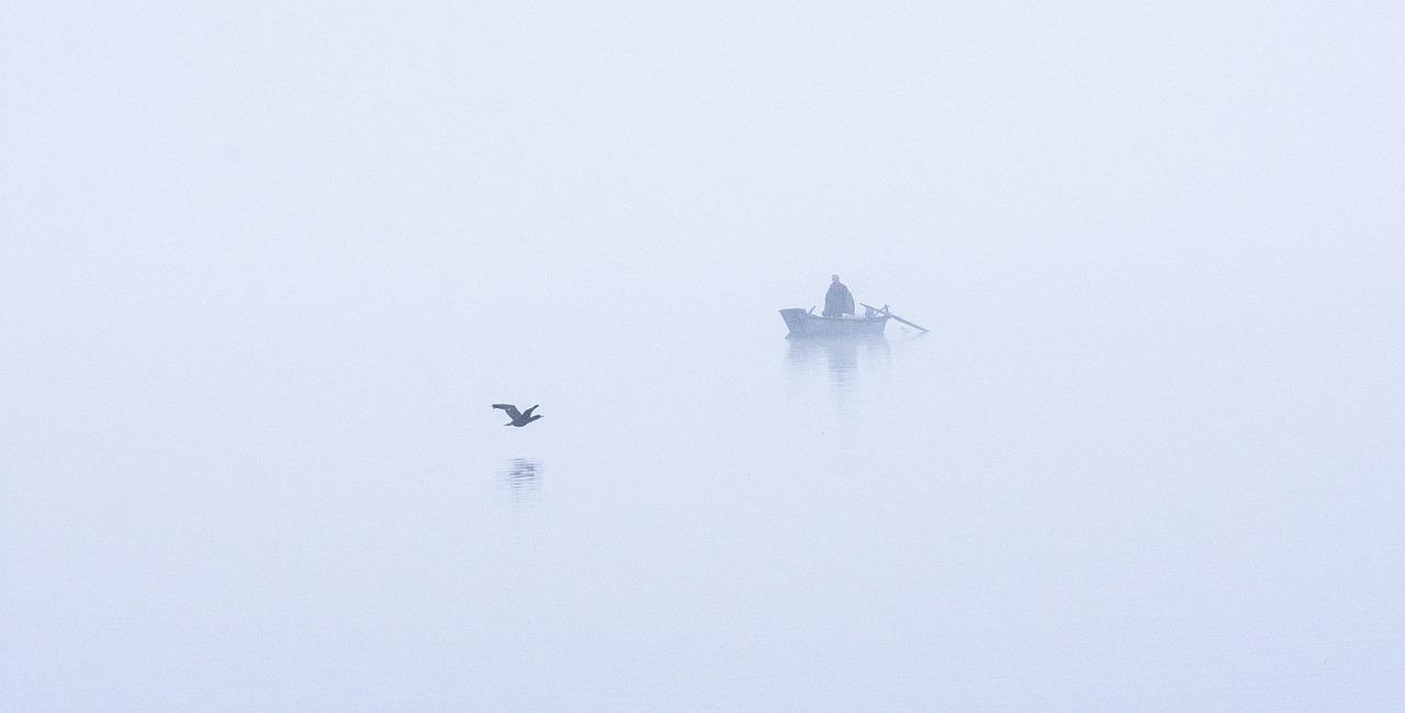 Ein Ruderboot im Nebel als Sinnbild für den magischen Jahresrückblick im Nebel unserer Gedanken