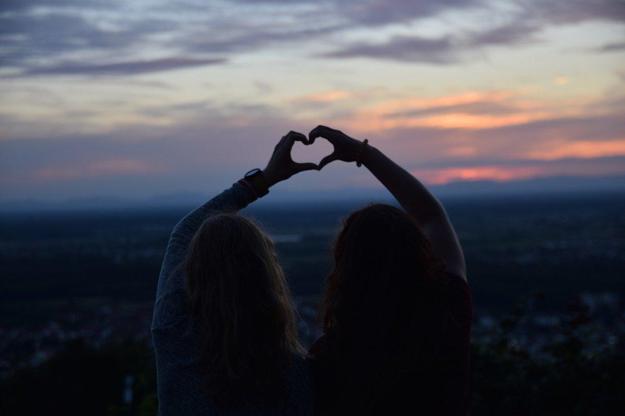 Zwei Mädchen halten ihre Hände als Herz gemeinsam in den dunklen Abendhimmel