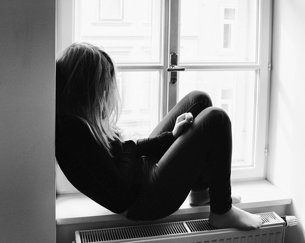 Frau sitzt zusammengesunken im Fenster als Sinnbild für den Schmerz von Trauma