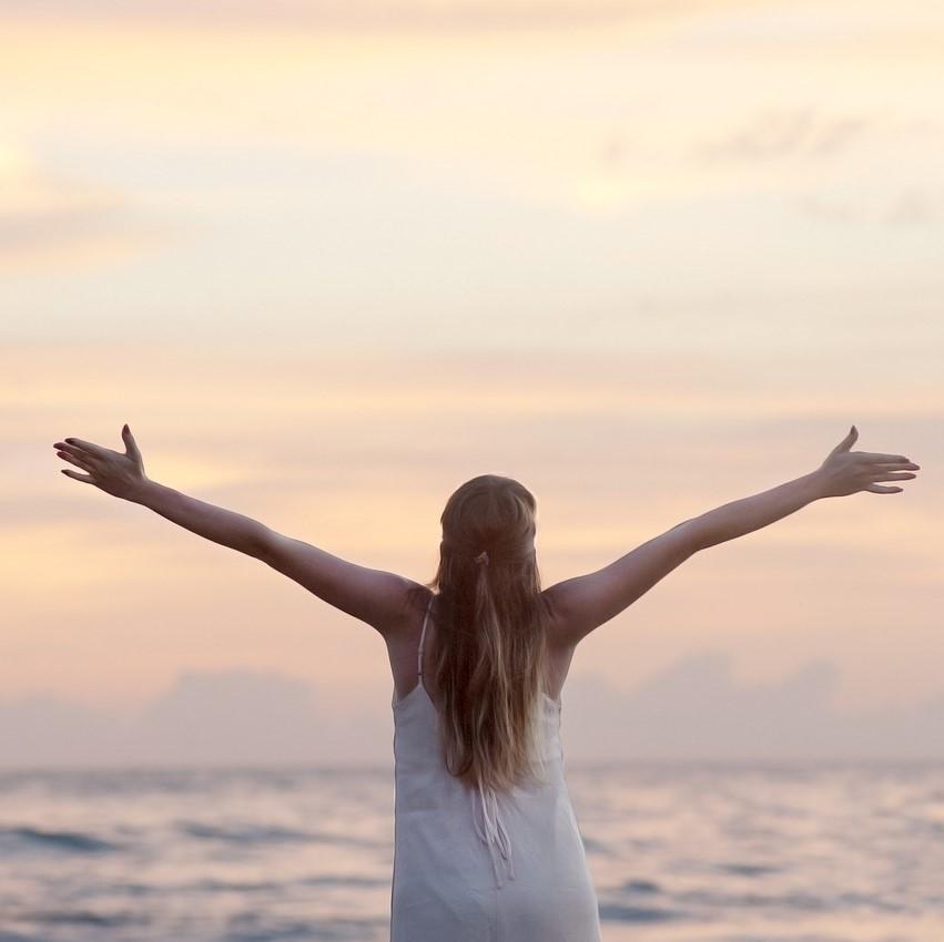 Frau mit ausgebreiteten Armen voller Glück am Meer