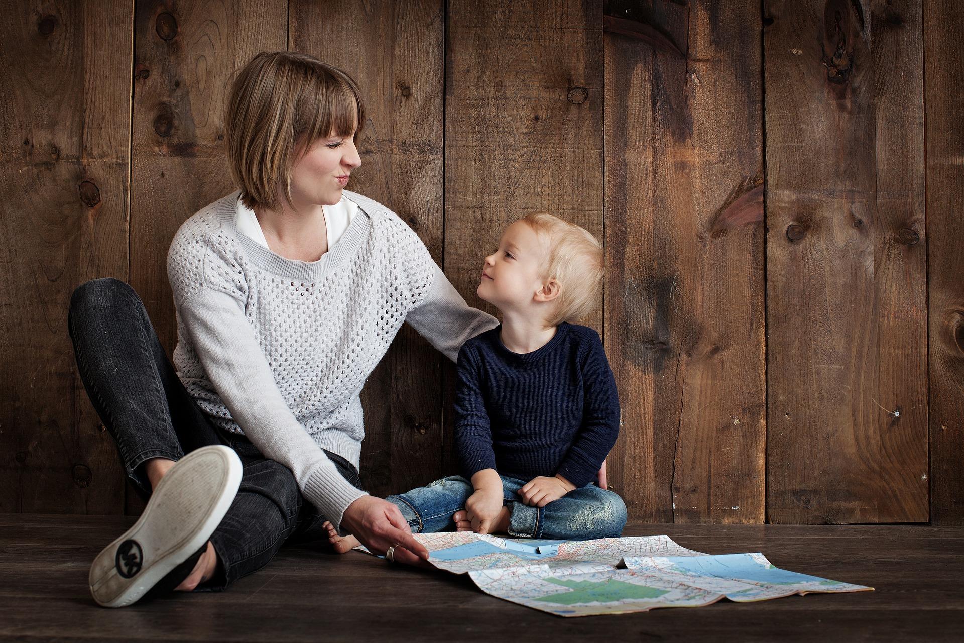 Mutter und kleines Kind sitzen auf dem Boden und schauen sich an