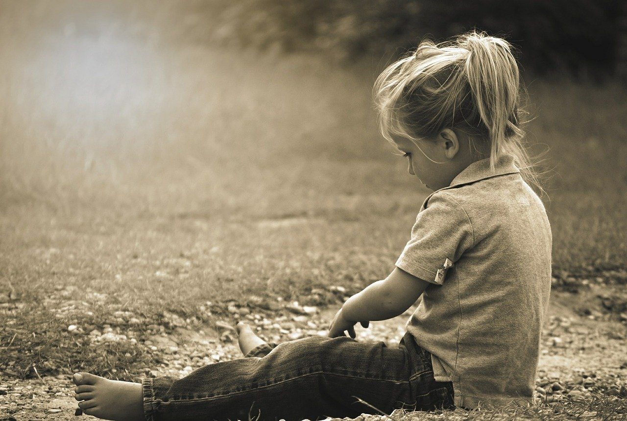 Trotziges Kind sitzt am Boden als Sinnbild für das trotzige innere Kind