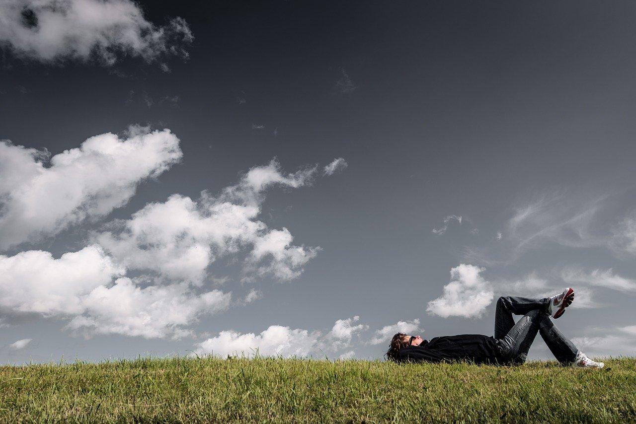 Mann liegt im Gras und schaut in die Wolken als Sinnbild für eigene Träume und die Löffelliste