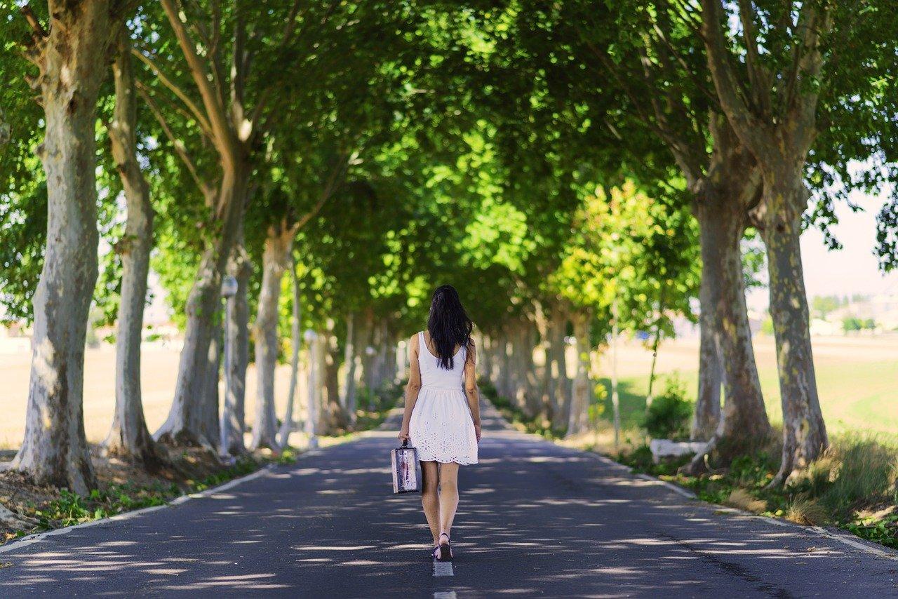 Frau mit einem Koffer läuft eine Alle entlang