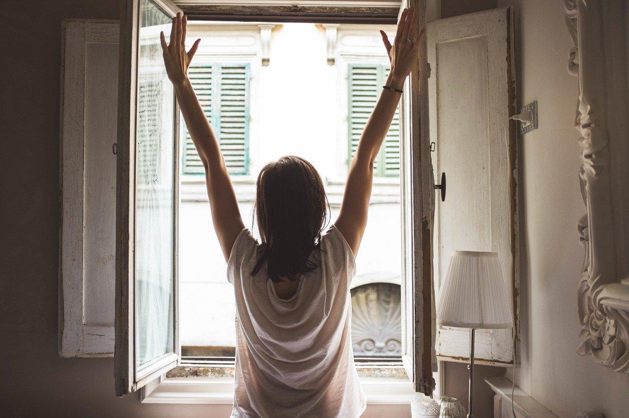 Frau am Fenster als Sinnbild für eine kraftvolle Morgenroutine