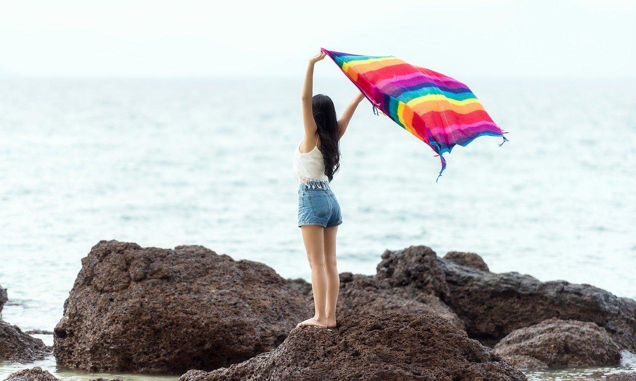 Junge Frau hält auf einem Felsen ein Handtuch in die Luft als Sinnbild für die Gedanken in uns