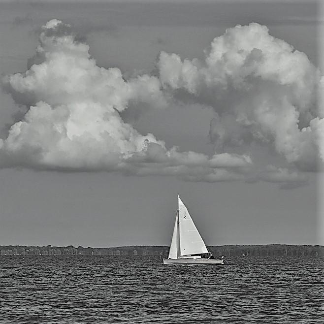 Segelboot mit Wolken über sich ls Sinnbild für einen Motivationsspruch