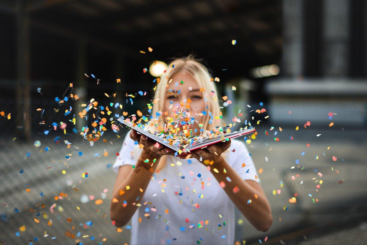 Frau pustet Konfetti aus einem Buch als Sinnbild für Motivation auf der Arbeit
