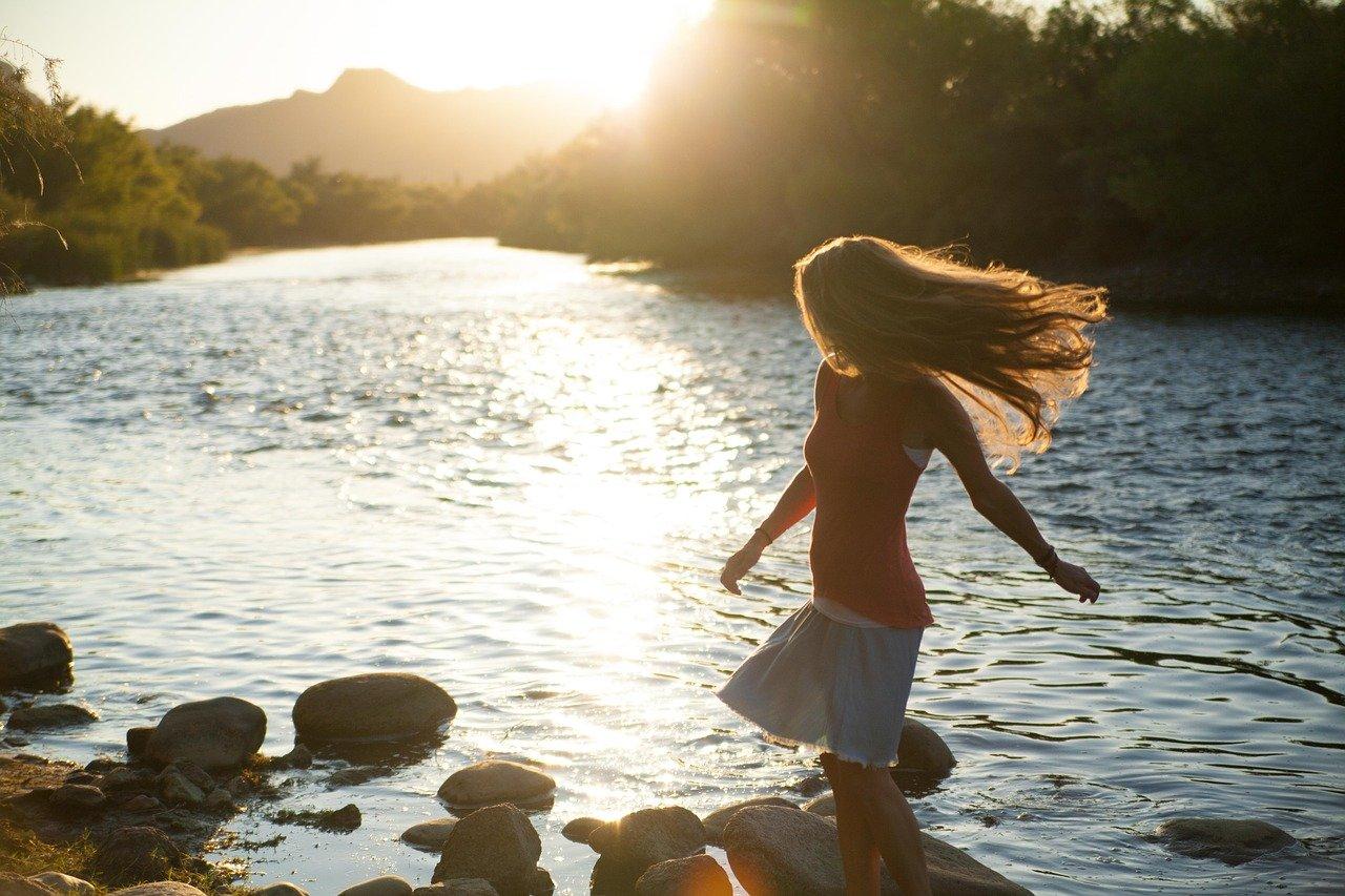 Frau an einem Fluss die tanzt als Sinnbild für sich selbst Wertschätzung geben