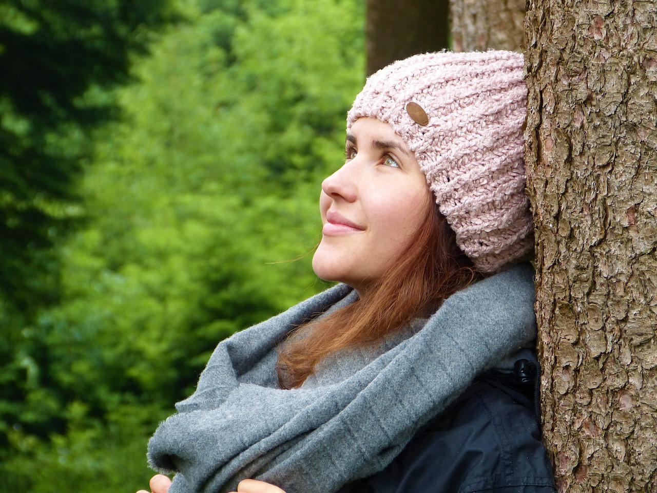 Junge Frau an einem Baum als Sinnbild für inneren Frieden